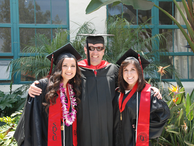 Carl Winston with two students in graduation robes